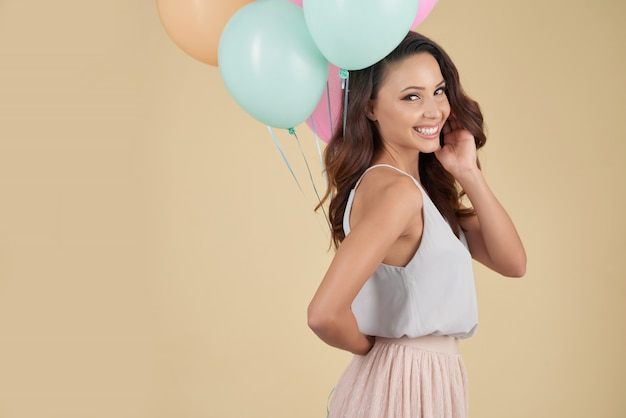 Senhora caucasiana sorridente posando no estúdio com balões e olhando por cima do ombro