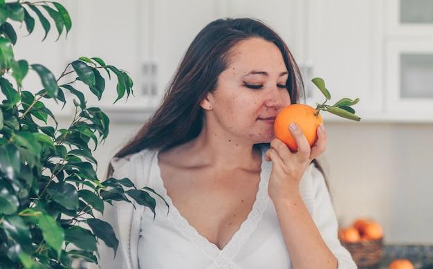 Senhora cheirando laranja na cozinha em jeans e camisa branca