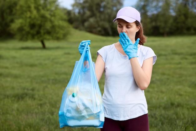 Senhora chocada, cobrindo a boca enquanto olha para o saco de lixo azul cheio de lixo coleta no prado