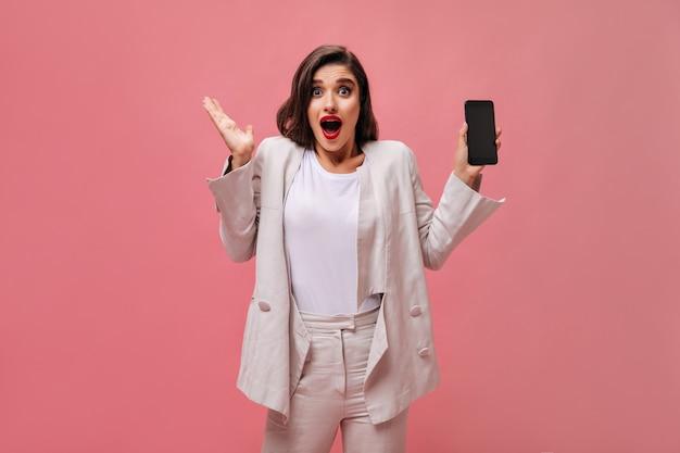 Senhora chocada em um terno de algodão demonstra telefone em fundo rosa. mulher surpreendida com lábios brilhantes em roupas brancas segura o telefone nas mãos.