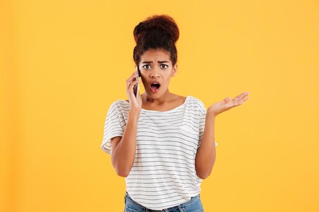 Senhora chocada falando no telefone