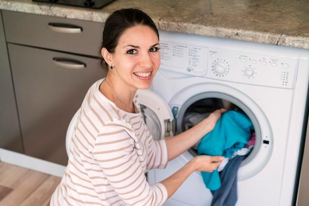 Senhora colocando as roupas na máquina de lavar