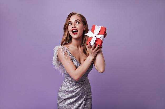 Senhora com bela maquiagem segurando uma caixa de presente na parede roxa