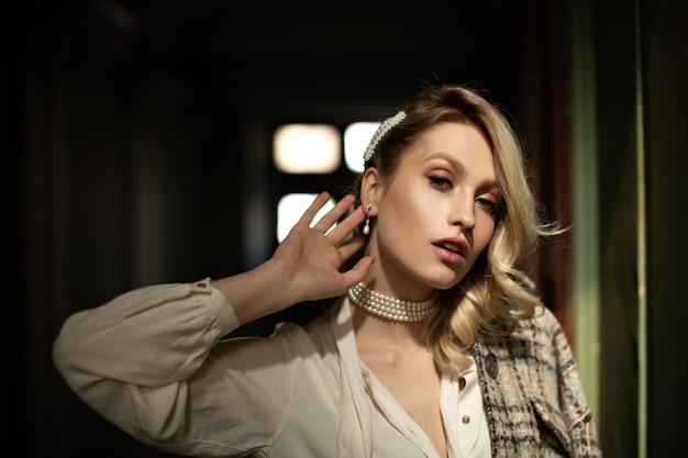 Senhora com bela maquiagem toca a orelha. mulher bonita loira com blusa branca e jaqueta xadrez olhando para a câmera em um quarto escuro
