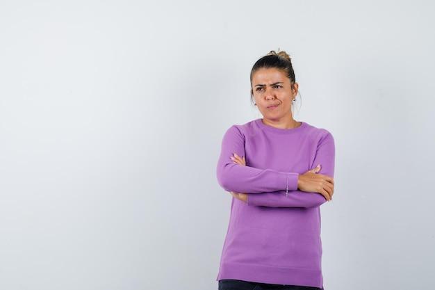 Senhora com blusa de lã com os braços cruzados e parecendo indecisa