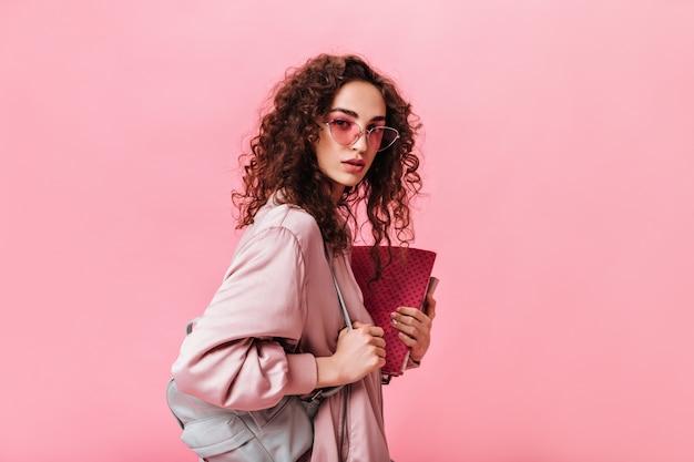 Senhora com cabelo ondulado olhando para a câmera e segurando livros