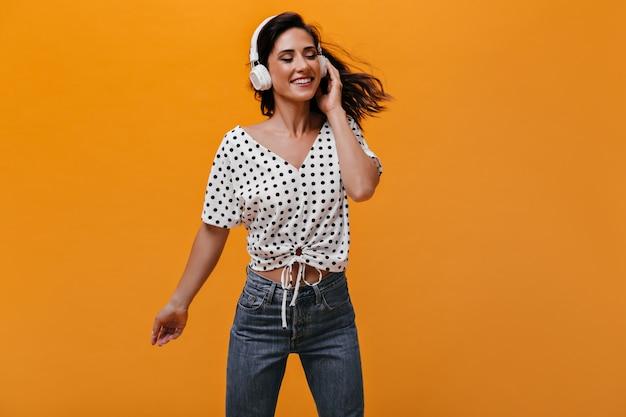 Senhora com camiseta de bolinhas curtindo música com fones de ouvido