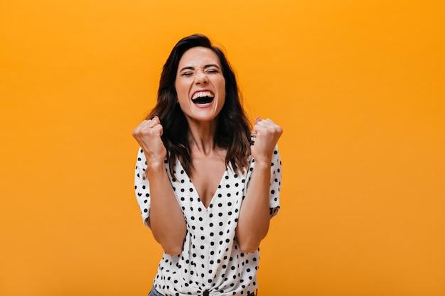 Senhora com camiseta de bolinhas posando alegremente em fundo laranja