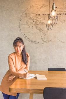 Senhora com caneta perto de mesa