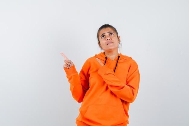 Senhora com capuz laranja apontando para o canto superior esquerdo e parecendo pensativa