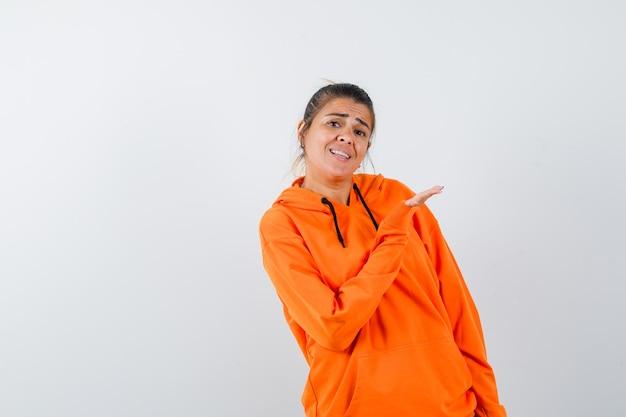 Senhora com capuz laranja apontando para o lado e parecendo alegre