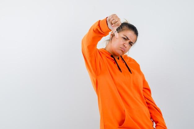 Senhora com capuz laranja mostrando o polegar para baixo e parecendo insatisfeita