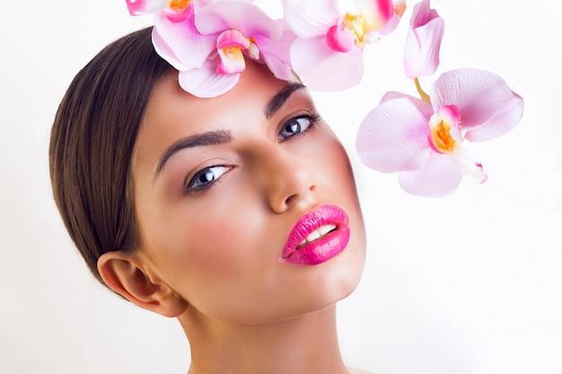 Senhora com flores de orquídea rosa, lábios grandes e maquiagem natural
