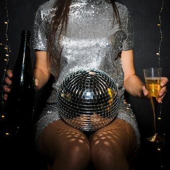 Senhora com garrafa de champanhe, vidro e bola de discoteca