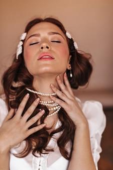 Senhora com grampos de pérola acaricia o pescoço com prazer. mulher de blusa branca, posando com os olhos fechados.