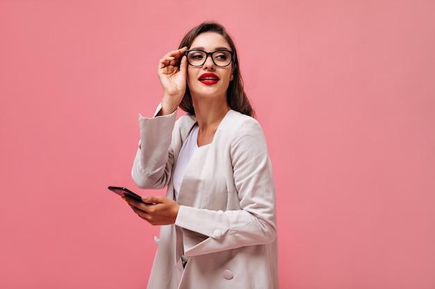 Senhora com lábios vermelhos, vestida com um terno de algodão, segura o telefone. jovem encantadora com cabelo escuro em óculos com aro preto, posando na câmera.