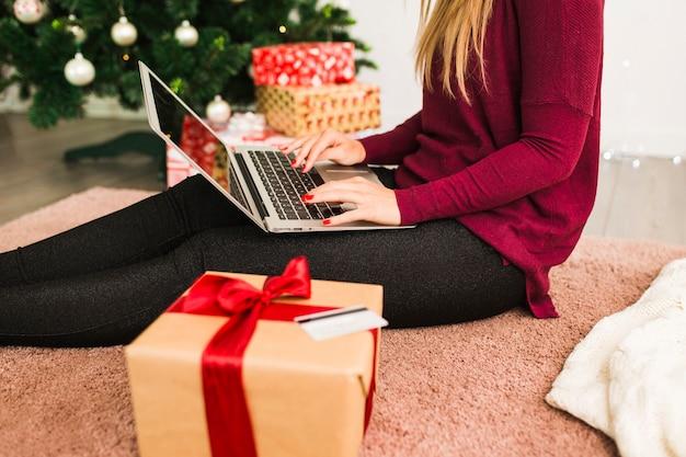 Senhora com laptop perto de cartão de crédito, caixa de presente e árvore de natal