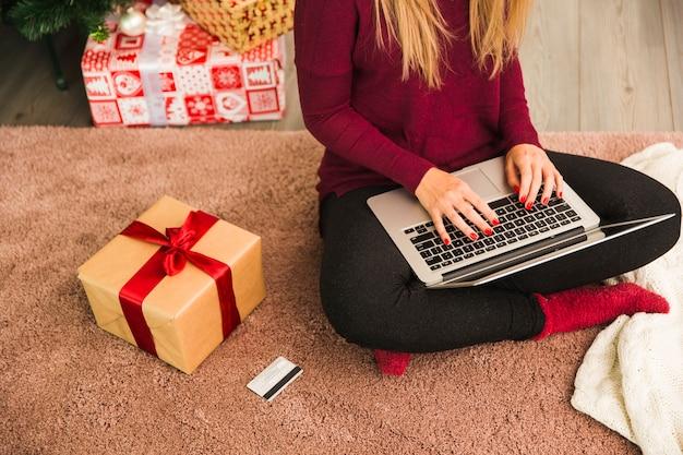 Senhora com laptop perto de cartão de plástico e caixas de presente