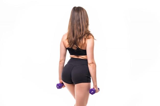Senhora com longos cabelos escuros faz exercícios para as costas com halteres azuis