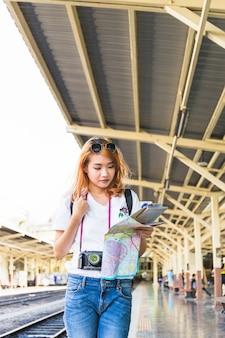 Senhora com mapa e câmera digital na plataforma
