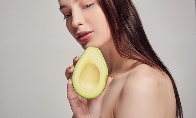 Senhora com marrom ouvir com abacate na mão