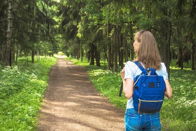 Senhora com mochila viajar na floresta.