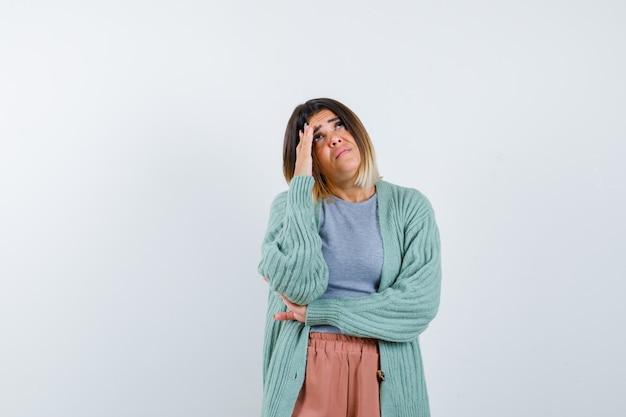 Senhora com roupas casuais, em pose de pensamento e parecendo preocupada, vista frontal.