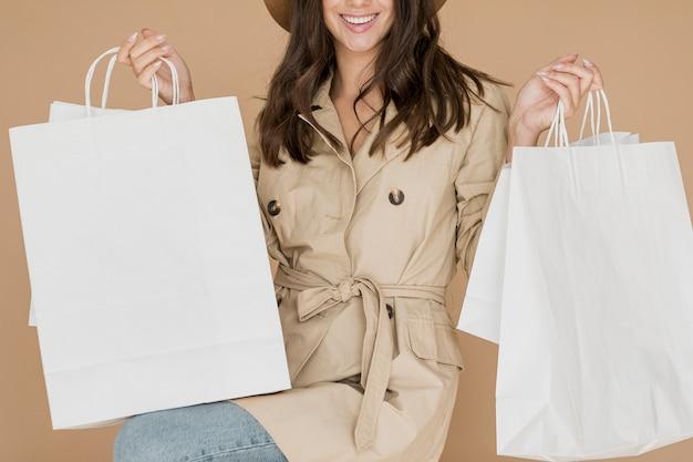 Senhora com sacolas de compras no fundo marrom