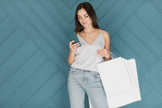 Senhora com smartphone vestindo jeans azul