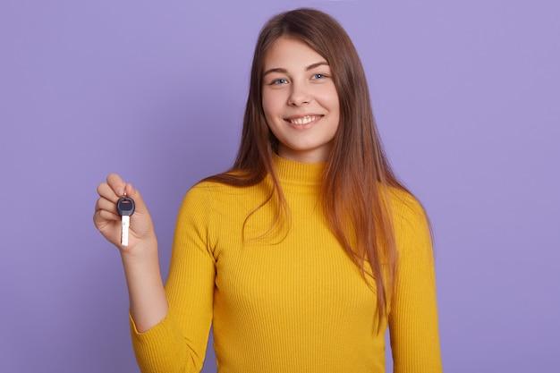 Senhora com sorriso encantador de pé contra a parede lilás, segurando a chave do carro