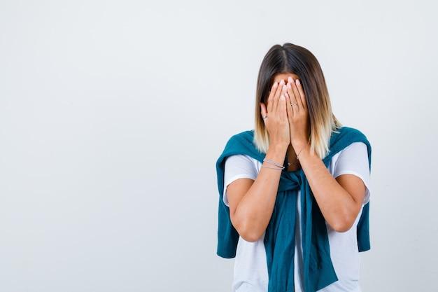Senhora com suéter amarrado em t-shirt branca cobrindo o rosto com as mãos e parecendo deprimido, vista frontal.