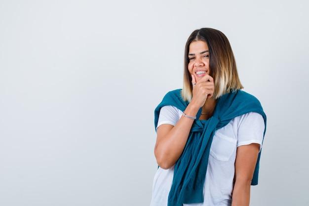 Senhora com suéter amarrado em t-shirt branca com a mão no queixo e parecendo alegre, vista frontal.