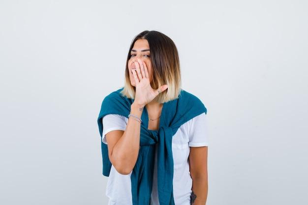 Senhora com suéter amarrado em t-shirt branca contando o segredo por trás da mão e parecendo curiosa, vista frontal.