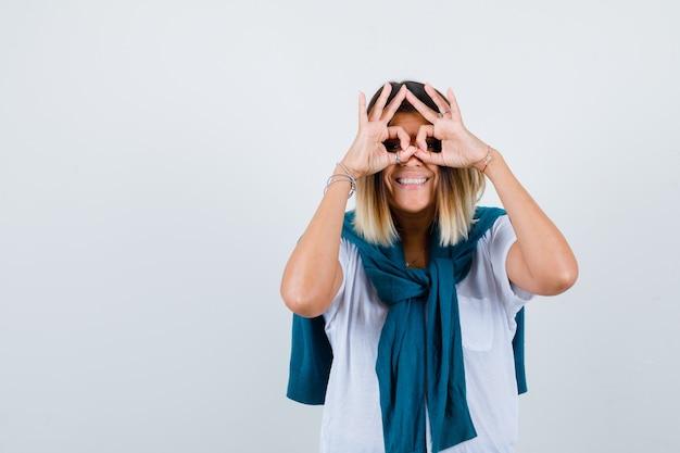 Senhora com suéter amarrado, mostrando gesto de óculos em t-shirt branca e olhando alegre, vista frontal.