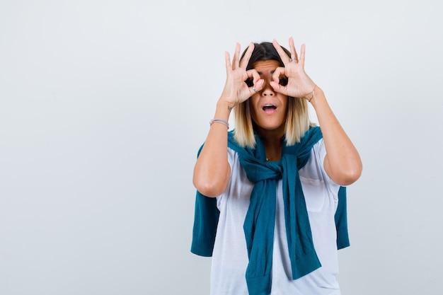 Senhora com suéter amarrado mostrando gesto de óculos em t-shirt branca e parecendo maravilhada. vista frontal.