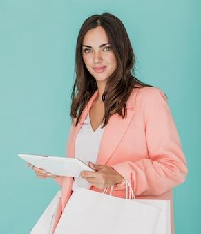 Senhora com tablet e sacolas de compras, olhando para a câmera