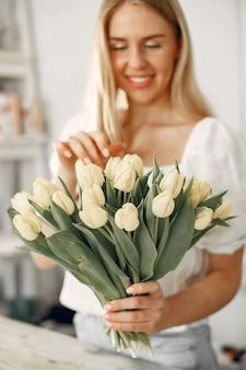 Senhora com tulipas. mulher faz um buquê.