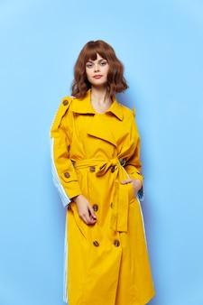 Senhora com um casaco amarelo com botões em um fundo azul com a mão no bolso