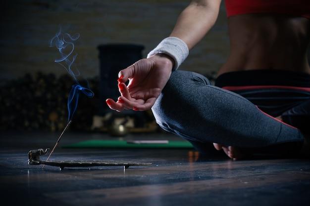 Senhora com unhas vermelhas sentada no chão com as pernas cruzadas em pose de meditação e tendo incenso ao lado dela