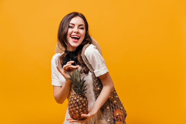 Senhora com vestido de verão de algodão ri e posa com abacaxi e saco ecológico em fundo laranja.