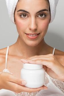 Senhora com vista frontal segurando uma garrafa plástica de creme