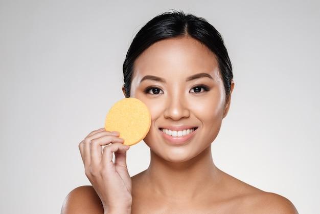 Senhora confiante atraente, limpando o rosto com almofada de algodão