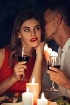 Senhora curiosa no vestido vermelho com copo de vinho, ouvindo seu homem bonito
