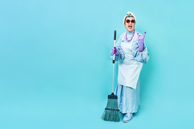 Senhora da limpeza fun. dona de casa funky idosa brincando com uma vassoura.