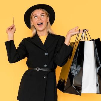 Senhora da moda de preto segurando sacolas de compras