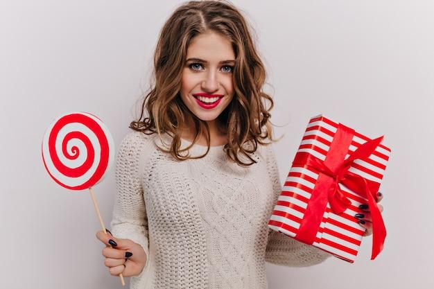 Senhora de 25 anos vestida com roupa de inverno quente com lábios vermelhos e cílios lindos segurando um presente de natal em uma caixa vermelha com fita. retrato de morena feliz com cachos longos