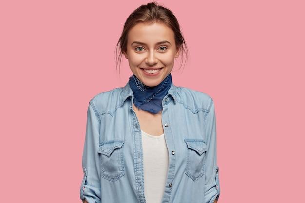 Senhora de aparência agradável, pele saudável, sorriso encantador, usa bandana no pescoço