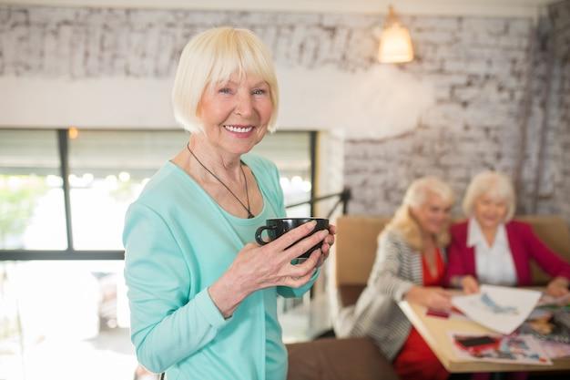 Senhora de azul. uma mulher loira em um terno azul em pé com uma xícara de chá nas mãos e sorrindo