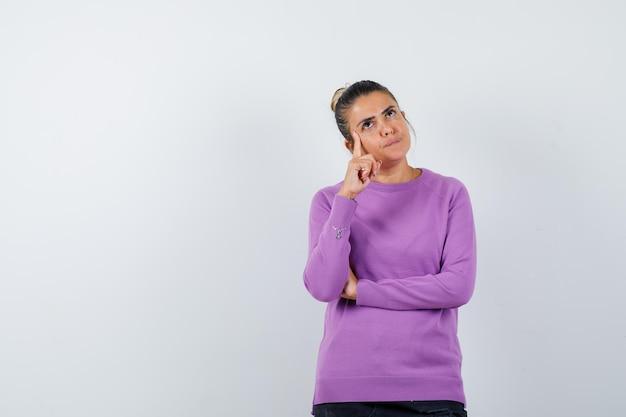 Senhora de blusa de lã com o dedo nas têmporas e parecendo indecisa