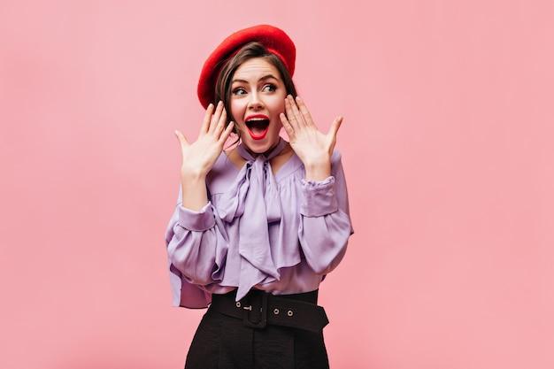 Senhora de blusa lilás e boina vermelha, agitando os braços e posando em alegre surpresa no fundo rosa.